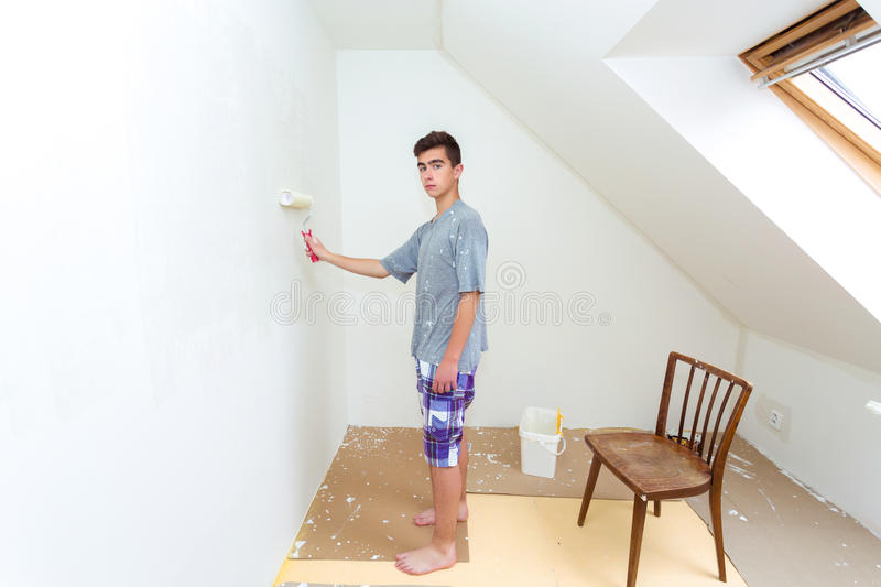 Teenager painting wall to white at home stock photo