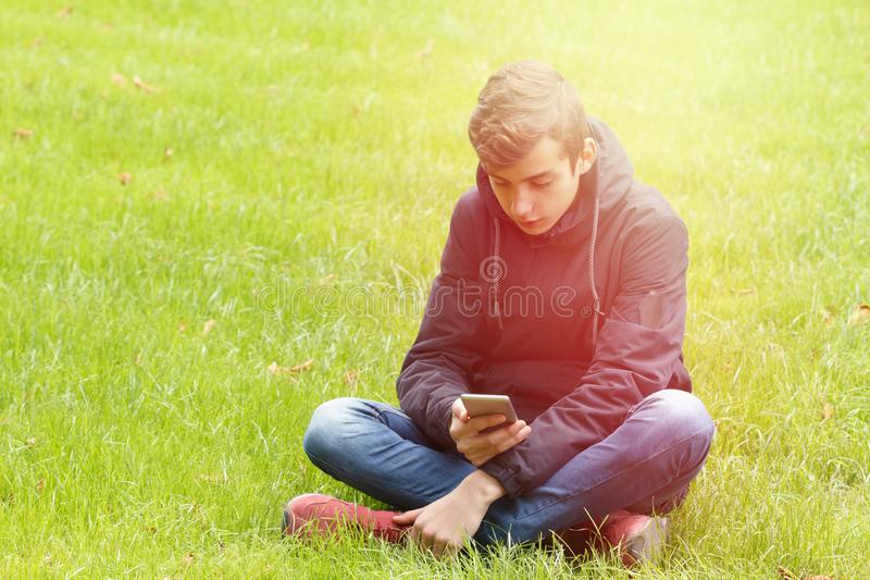 Teenager with a Phone in the Park. Teenager with a smart Phone in the Park outdoors stock photography