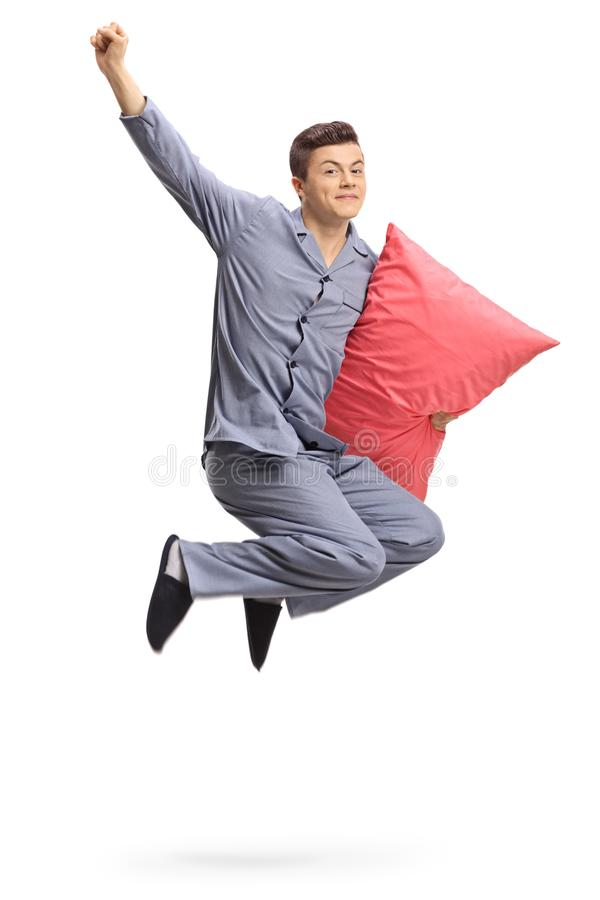 Teenager with a pillow jumping and gesturing happiness. Isolated on white background royalty free stock image
