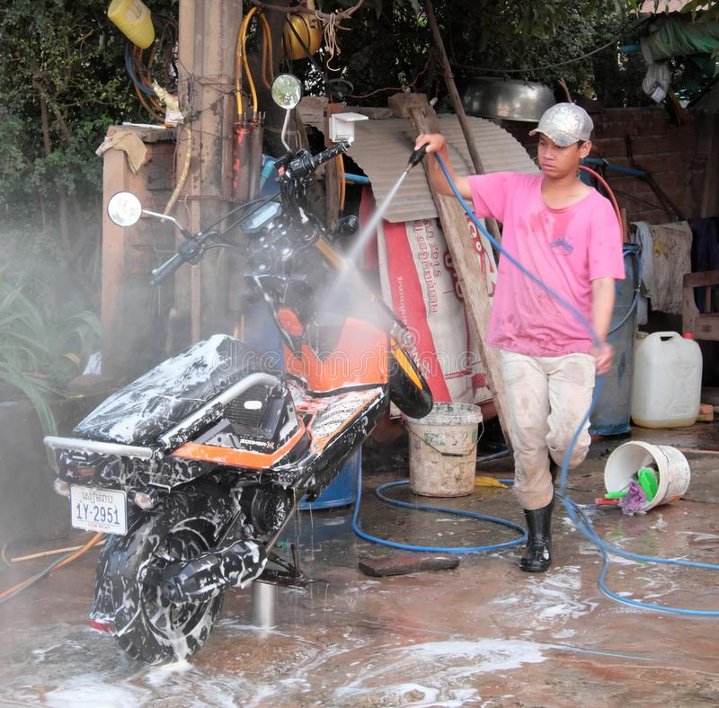 Siem Reap, Cambodia, December 17, 2018 teenager in a pink t-shirt, cap and rubber boots washes a scooter. Motor scooter in white. Soap suds. Wash vehicles with stock photo