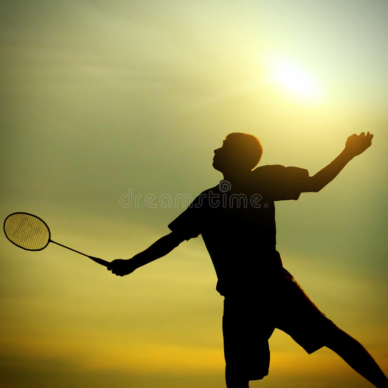 Teenager playing Badminton. Silhouette of Badminton Player against Evening Sky royalty free stock photo