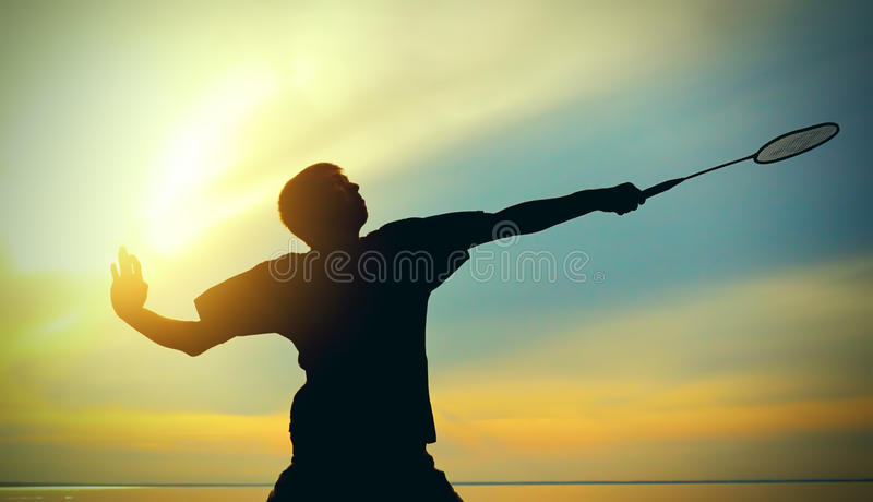 Teenager playing Badminton. Silhouette of Badminton Player against Evening Sky royalty free stock image