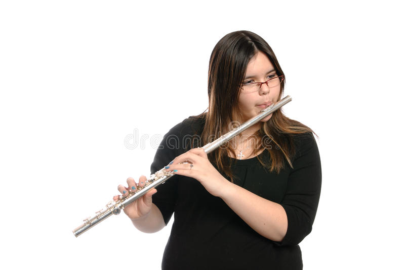 Teenager Playing Flute. A teenage girl is playing the flute, isolated against a white background stock images