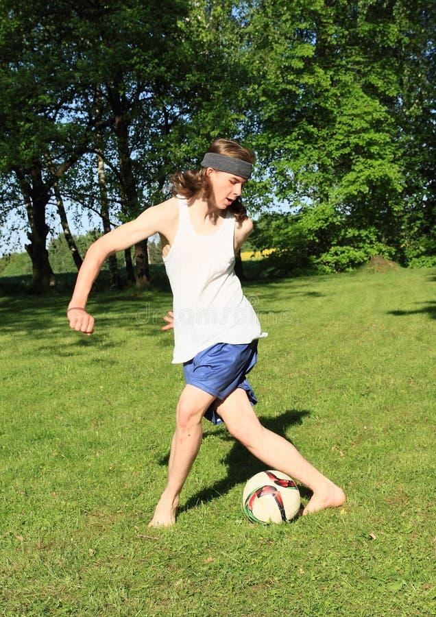 Teenager playing football stock image