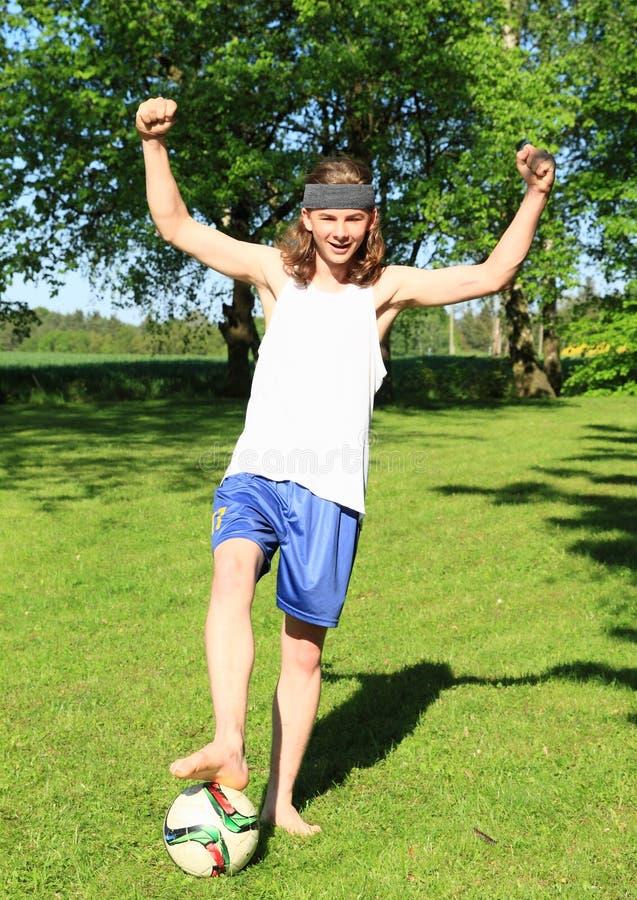 Teenager playing football - winner royalty free stock photo