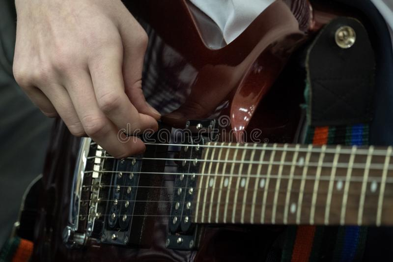Teenager plays the electric guitar. The fingers of a young bassist are pulling bass strings. Musical theme. Close-up stock photos