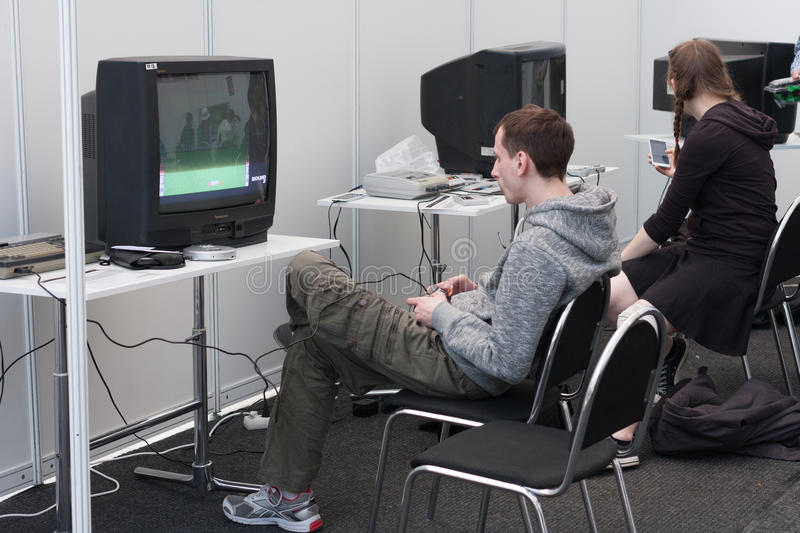 Teenager plays gaming console with television at Animefest royalty free stock images