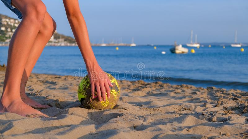 Teenager plays in the summer on a sunny day on beach with a ball royalty free stock photo