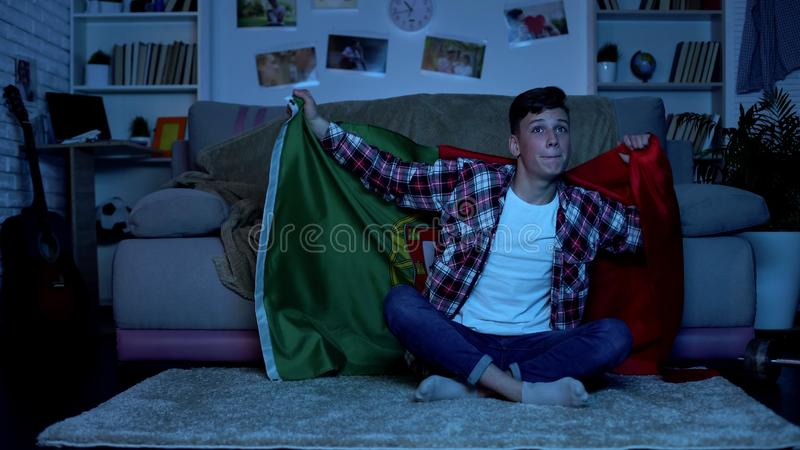 Teenager with Portuguese flag supporting national team home, sports competition stock image