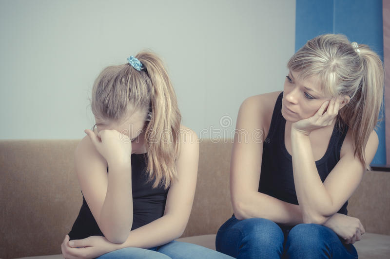 Teenager problems - Sad crying teenage girl and her worried mother.  royalty free stock photo