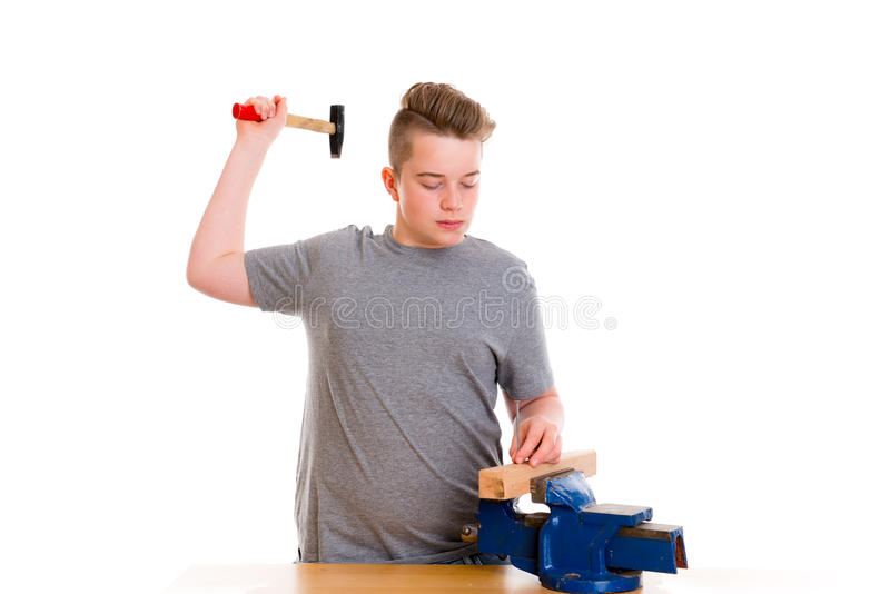 Teenager in professional training with hammer stock photos