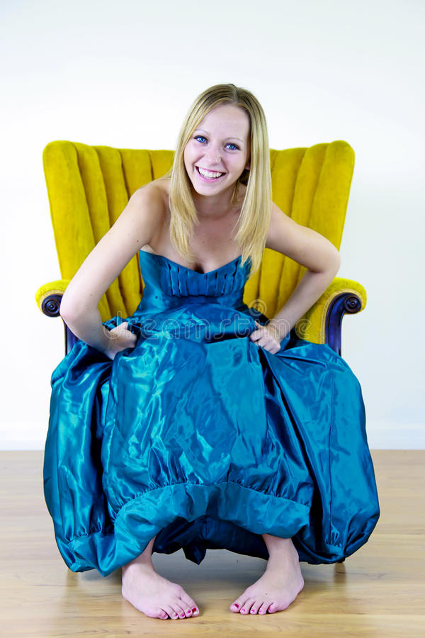 Teenager in prom dress. Pretty teenager sat in chair wearing blue prom dress, studio background royalty free stock image