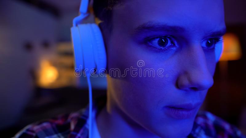 Teenager putting earphones on and playing video game, cybersports leisure royalty free stock photos