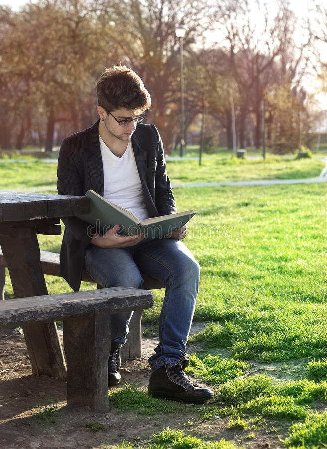 Teenager reading book. In park stock photos