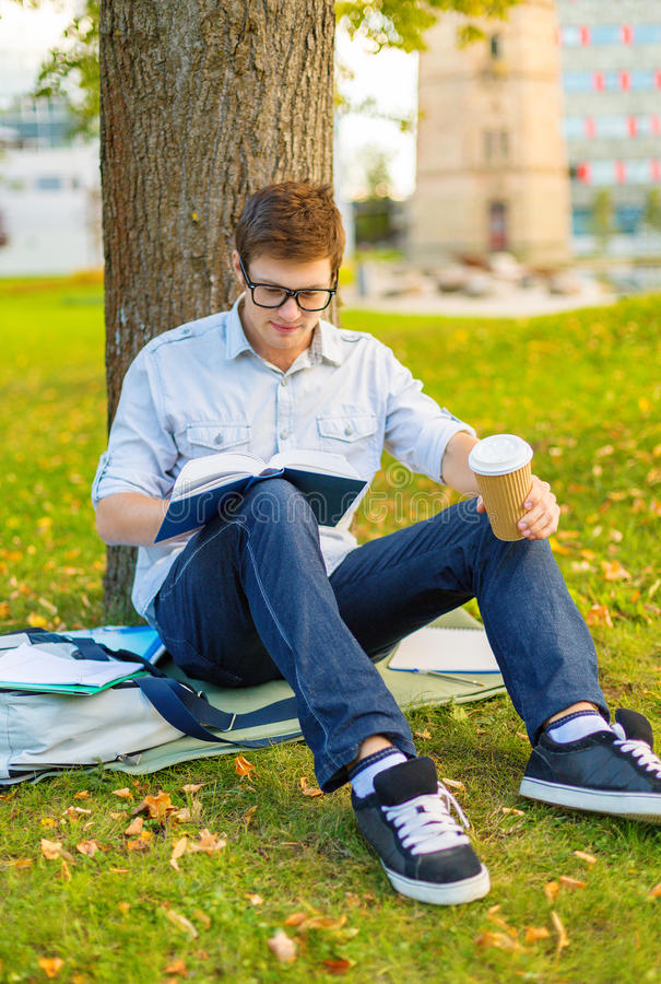 Teenager Reading Book With Take Away Coffee Stock Photo