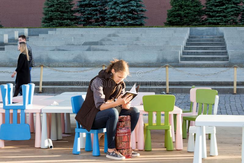 Teenager reads a book just bought at a book festival. Moscow, Russia, 02 June 2018: Open Book Fair on the Red Square in Moscow - big festival of books. A stock photography