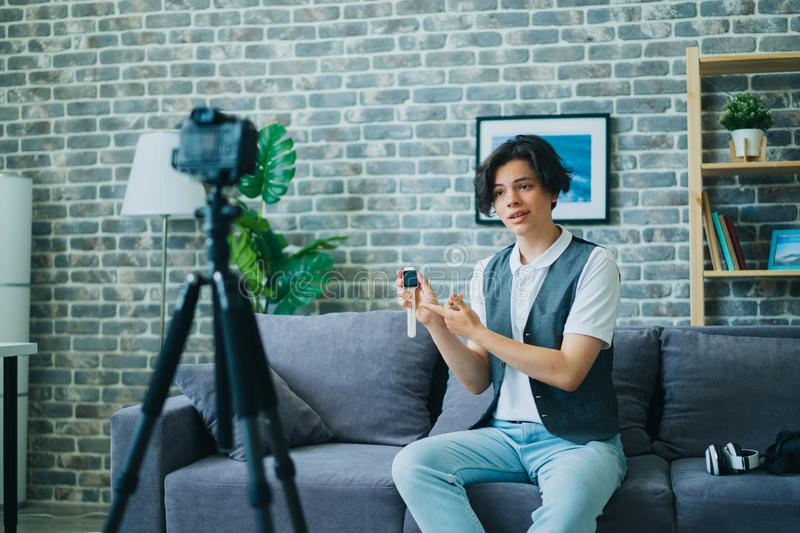 Teenager recording video about modern watch holding gadget talking for camera royalty free stock photos