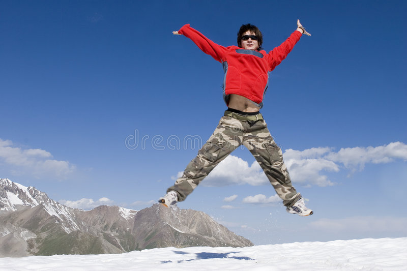 Teenager in red in sport hike. Teenager jumping in red sport pullover in mountain hike and blue sky royalty free stock photos