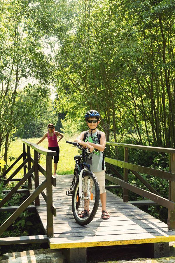 Download Teenager Relaxing On A Bike Trip On Wooden Bridge Stock Image - Image of helmet, cycle: 32922783