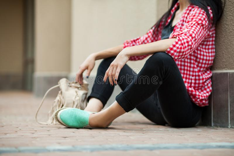 Teenager resting on the ground. Young teenager resting on the ground with closen eyes, leaning against the wall. Concept of modern freedom hipster human, close royalty free stock image