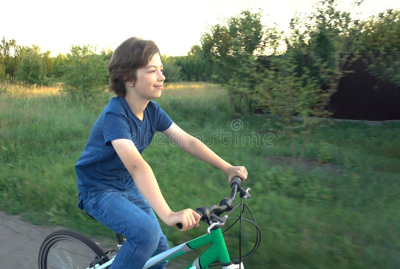 Teenager riding a bicycle on the road summer sunlit royalty free stock photos