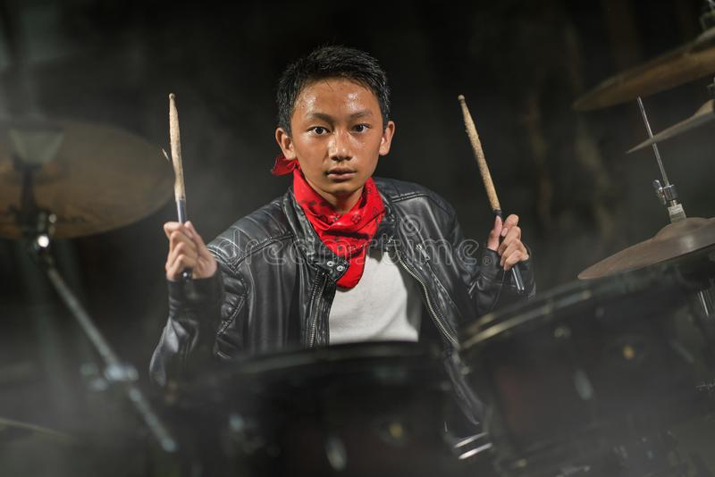 Teenager rock band musician . 13 or 14 years old cool and talented Asian American mixed ethnicity boy playing drums in leather royalty free stock photos