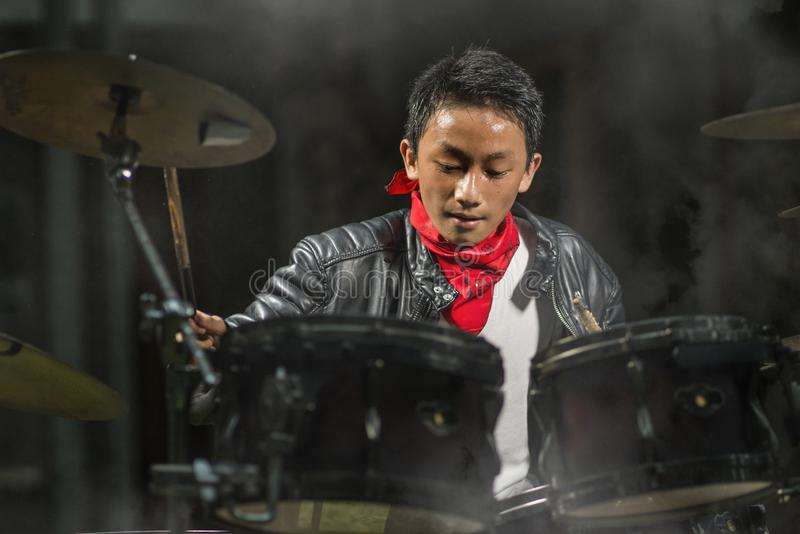 13 or 14 years old cool and talented Asian American mixed ethnicity boy playing drums in leather jacket and bandana  practicing stock image