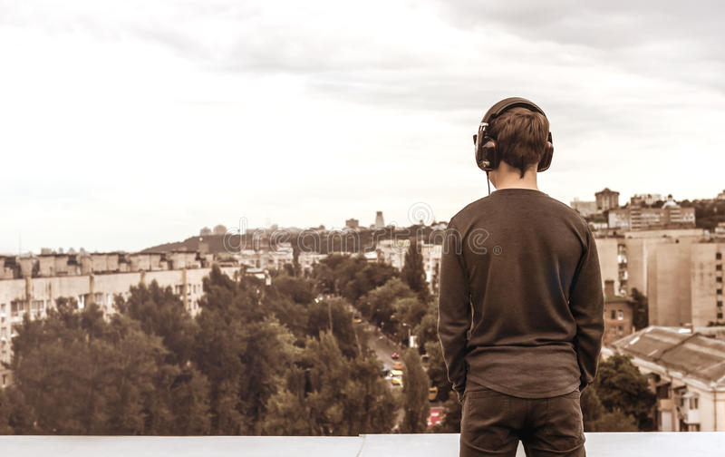 Teenager on the roof of the house in the headphones. Teenager on the roof of the house listens to music stock photo