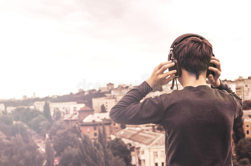 Teenager on the roof of the house in the headphones. Teenager on the roof of the house listens to music stock photography