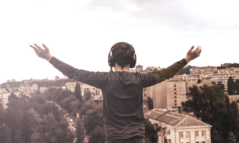 Teenager on the roof of the house in the headphones. Teenager on the roof of the house listens to music royalty free stock photo