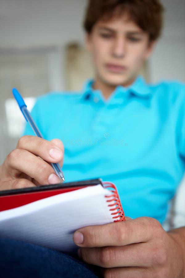 Teenager saß Schreiben im Notizbuch stockfoto