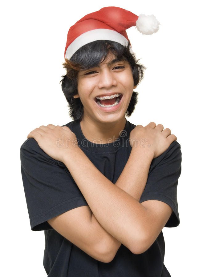 Teenager Santa portrait. Portrait of Indian male teenager with arms crossed on shoulders, with teeth braces and Santa Claus hat laughing loud. Isolated over stock images