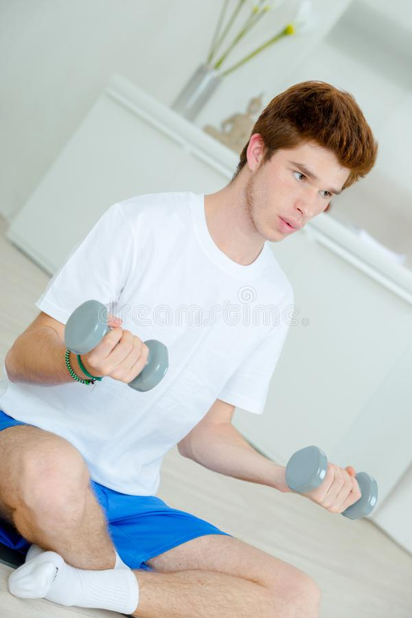 Teenager sat doing weights royalty free stock photography