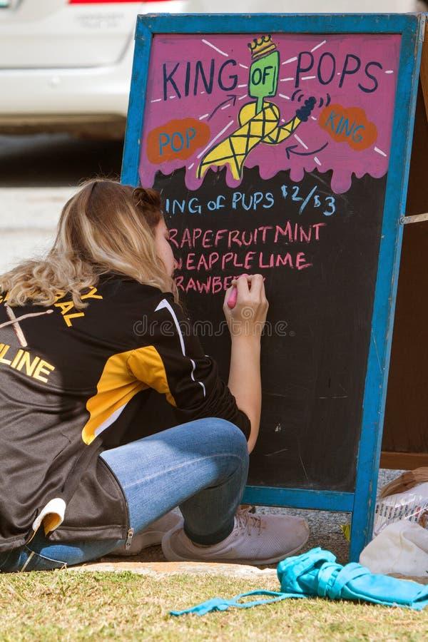 Teenager scrive i sapori del ghiacciolo sulla lavagna prima dell'evento al parco immagini stock libere da diritti
