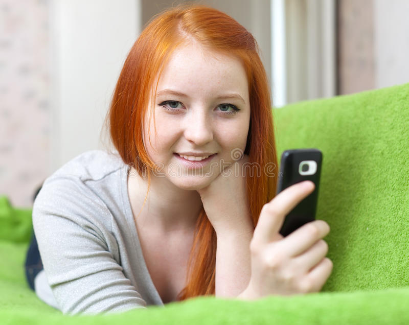 Teenager sends SMS. On her mobile in home stock photo