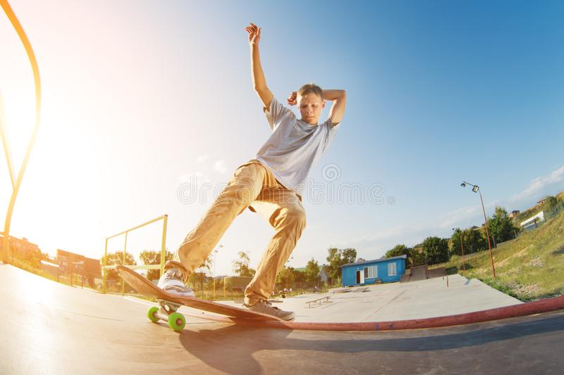 A teenager in shorts and a cap does an allie stunt on a ramp in a skate park in a residential area in summer sunset. The royalty free stock image