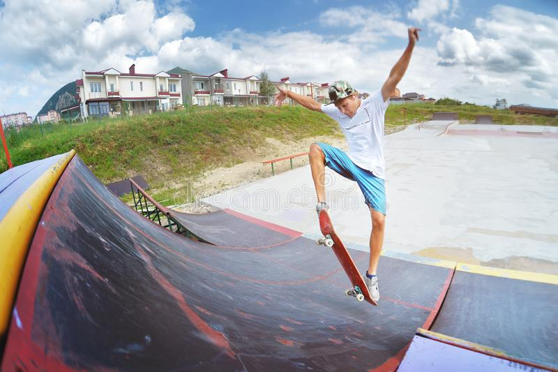 A teenager in shorts and a cap does an allie stunt on a ramp in a skate park in a residential area in summer. The royalty free stock photos