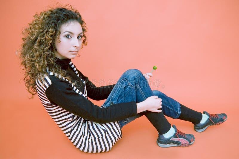 Teenager si siede contro una priorità bassa arancione fotografie stock libere da diritti