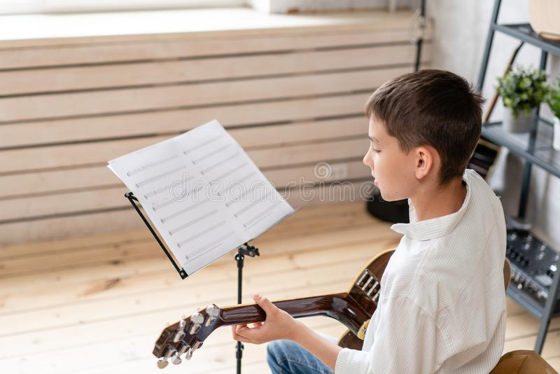 Teenager sits in chair behind sheet music and learning new melody for acoustic guitar stock images