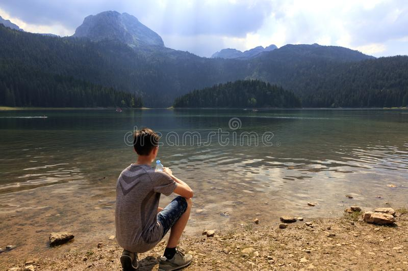 A teenager sits on the shore of a mountainous lake clean with a bottle of water royalty free stock photo