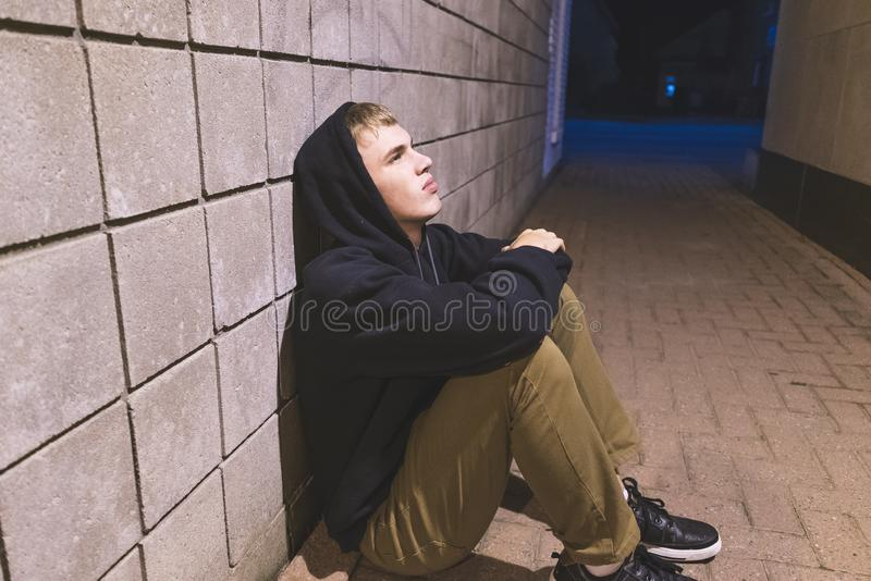 Teenager sitting in an alleyway. royalty free stock image