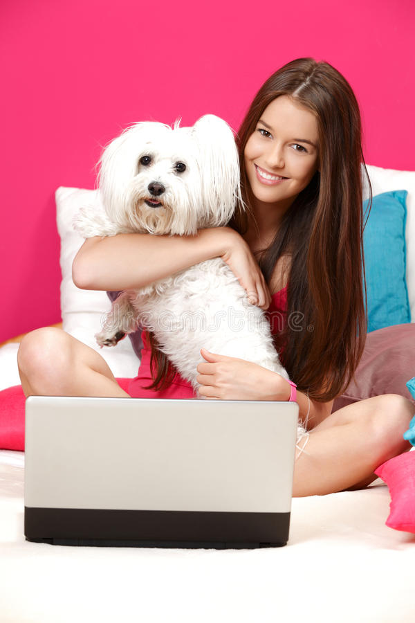 Teenager sitting in her bed with her white dog royalty free stock photos