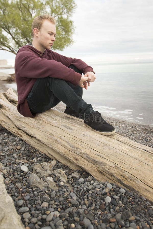 Teenager sitting on log and thinking stock photography