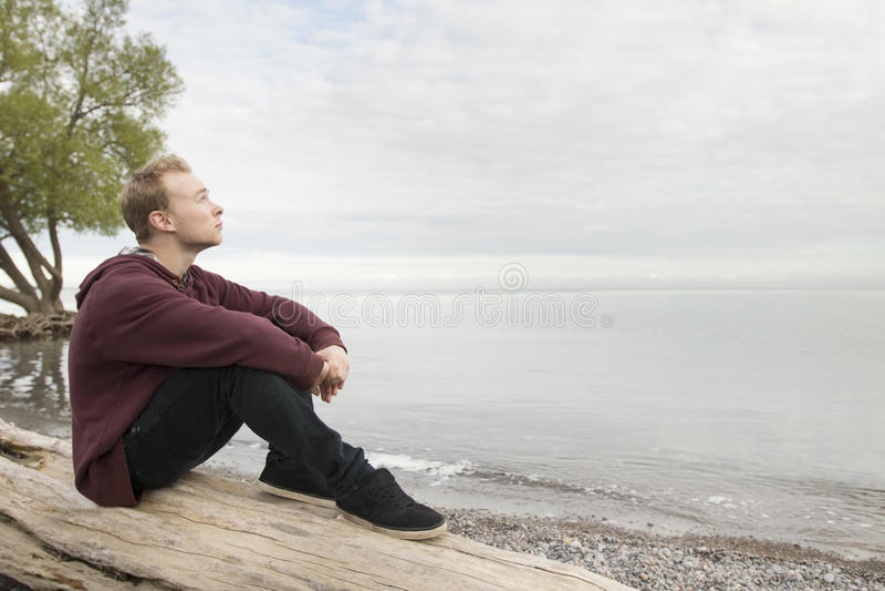 Teenager sitting on log and thinking stock photo
