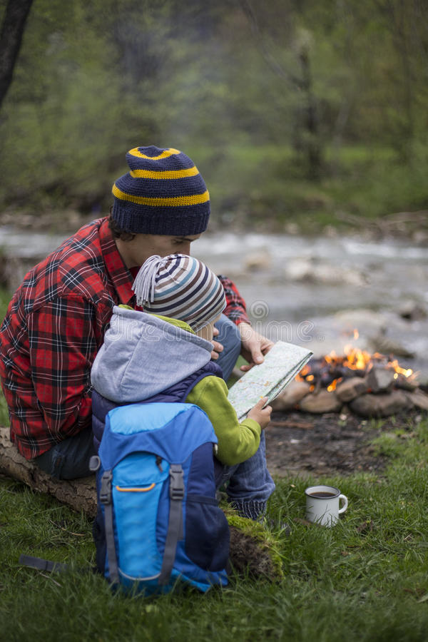 Teenager sitting near a fire in camping and watching map. royalty free stock image
