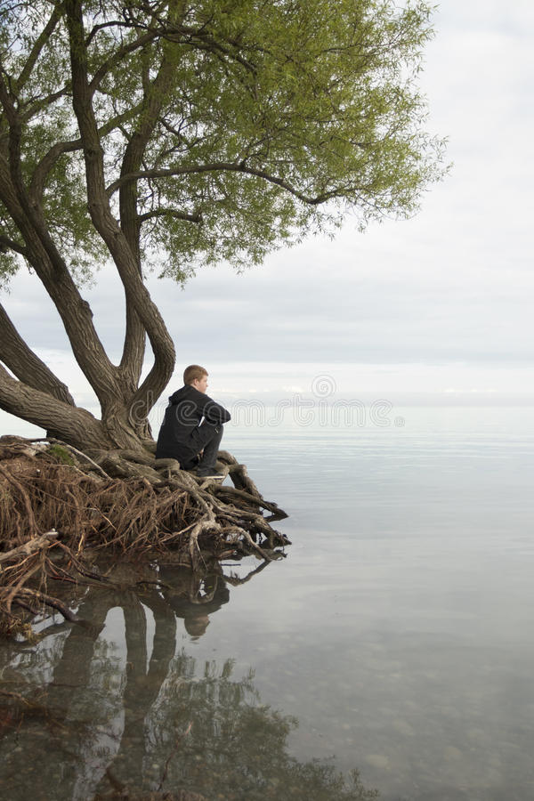 Teenager sitting on roots and thinking royalty free stock photography