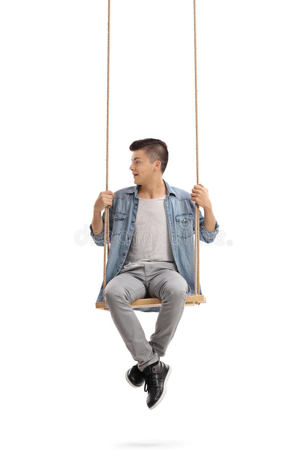 Teenager sitting on a swing and looking to the left royalty free stock photography