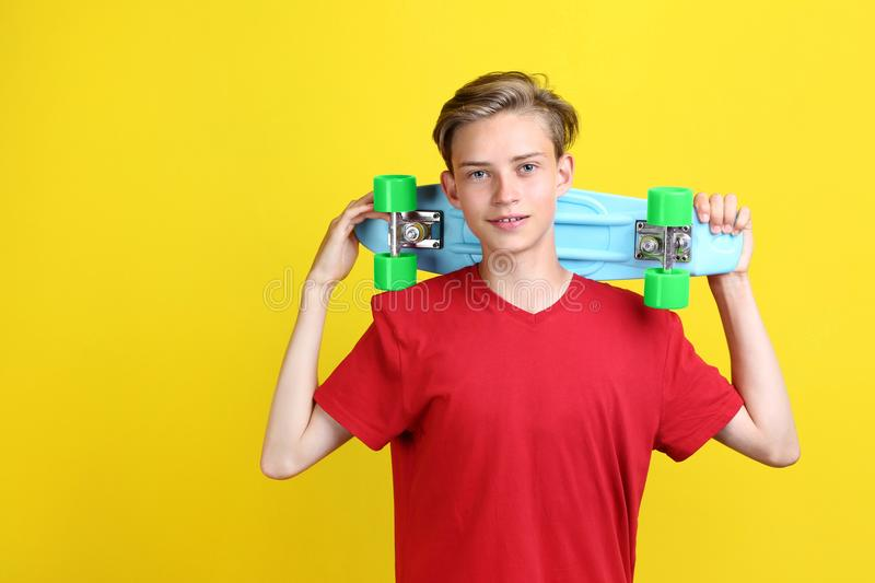 Teenager with skateboard. Cute teenager with skateboard on yellow background stock photography