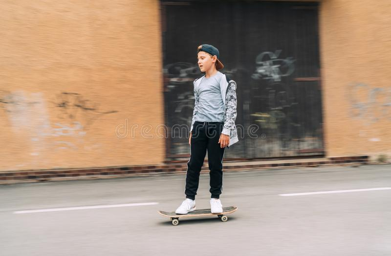 Teenager skateboarder boy riding on skateboard on asphalt road near a grunge graffiti wall. Youth generation Freetime spending royalty free stock image