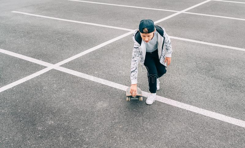 Teenager skateboarder boy with a skateboard on asphalt playground doing tricks. Youth generation Freetime spending concept image royalty free stock photography